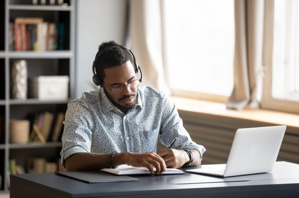 Concentrated biracial guy listening to favorite music while planning workday.